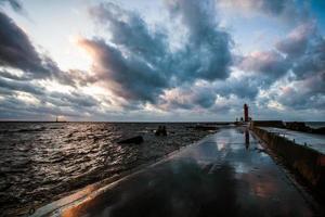 fragmento de quebra-mar com mar visível e farol. foto