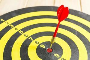 flecha de dardo vermelho, acertando no centro do alvo de alvo foto