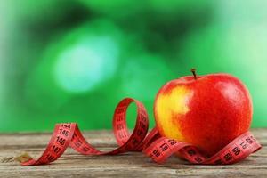 maçã vermelha com fita métrica em fundo cinza de madeira foto
