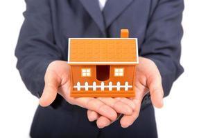 mãos, apresentando um pequeno modelo de casa foto