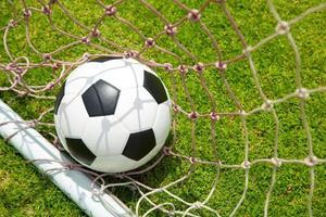 bola de futebol no gol após tiro foto