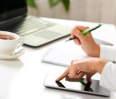 mãos de mulher com tablet pc e bloco de notas no escritório foto