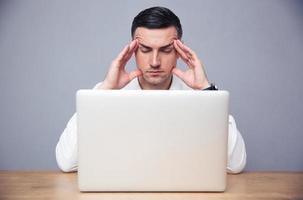 empresário pensativo, sentado à mesa com o laptop foto