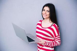mulher muito sorridente em pé com o laptop foto