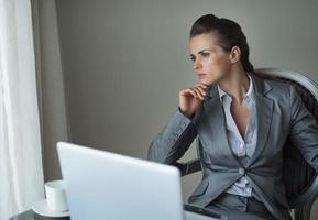 mulher de negócios pensativo trabalhando no laptop no quarto de hotel
