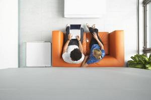 casal usando laptop no sofá laranja no escritório