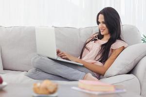 morena atraente usando seu laptop foto
