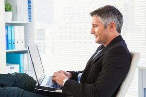 empresário alegre usando laptop e relaxante foto