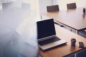 local de trabalho através da porta de vidro aberta com laptop, smartphone e café foto