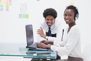 colegas de trabalho sorridente usando laptop foto