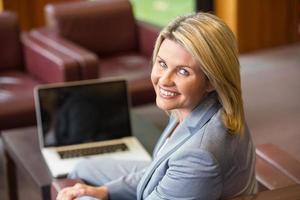 empresária loira sorrindo usando laptop foto