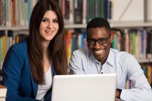 alunos usando um computador tablet em uma biblioteca foto