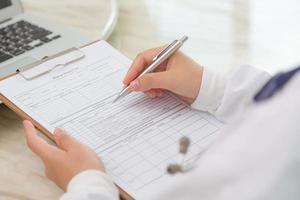 mão de médico escrevendo sobre prescrição foto