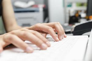 dedos no teclado do laptop foto