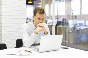 homem trabalhando em seu laptop no escritório na inicialização foto