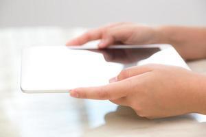 mulher mão tocar pastilha branca com tela vazia em branco foto