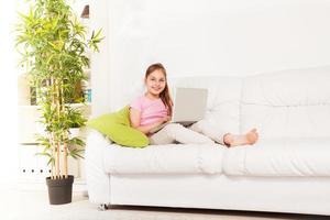 menina com laptop no sofá foto