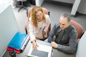 colegas de trabalho olhando para o computador no escritório foto