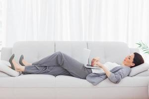 empresária usando seu laptop deitado no sofá foto