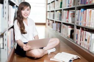 bela aluna asiática estudando na biblioteca com o laptop