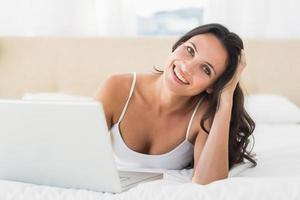 morena feliz usando seu laptop foto