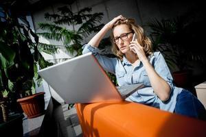 linda jovem empresária usando telefone celular. foto