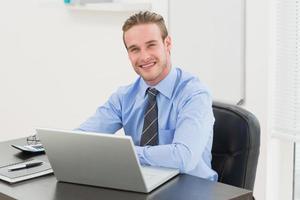 alegre empresário elegante usando laptop foto