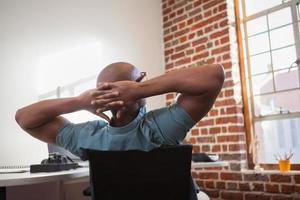 empresário casual, inclinando-se para trás na cadeira foto