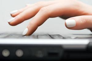 mãos femininas digitando no teclado do computador foto