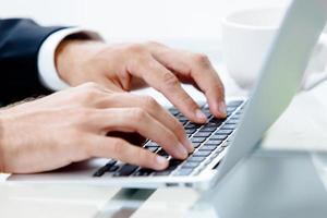 mãos do homem no teclado do laptop foto