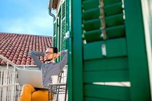 homem com laptop na varanda foto