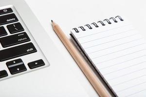 laptop, bloco de notas e lápis, o instrumento do blogueiro foto