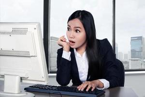 mulher feliz sorridente usando o computador foto