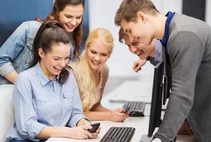 alunos com monitor de computador e smartphones foto