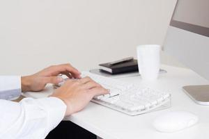 mãos do empresário com um teclado de computador. foto