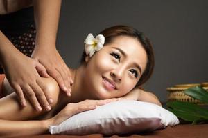 mulher asiática recebendo massagem compressa de ervas tailandesas no spa.