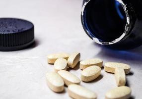 pílulas / comprimidos de vitaminas e minerais com vista lateral para o frasco foto