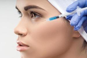 jovem mulher caucasiana, recebendo injeção plástica foto