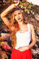 linda menina com um buquê de folhas de trevo no outono foto
