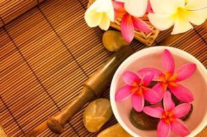 spa tropical com flores de frangipani na água.