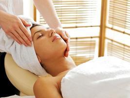 jovem mulher recebendo massagem facial, olhos fechados foto