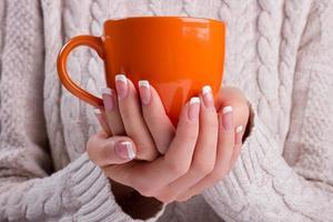 mulher mantém uma xícara de inverno fechar.