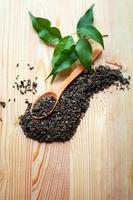chá verde em colher de pau e folhas de chá foto