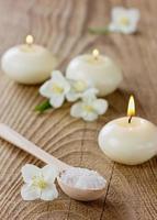 composição de spa com banho de sal marinho, flores de jasmim e velas