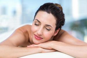 morena sorridente relaxante na mesa de massagem foto