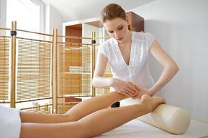 jovem mulher recebendo massagem nos pés de massagista foto