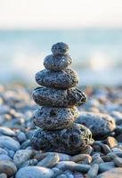 monte de pedras na praia do mar de seixos foto
