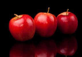 três frutas de maçã vermelha em fundo preto foto