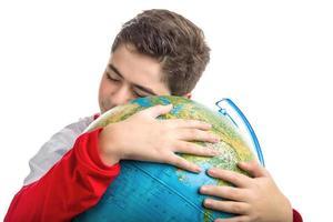 menino caucasiano abraça o globo foto