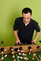 homem caucasiano jogando pebolim, matraquilhos foto